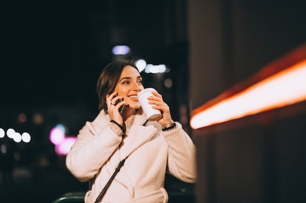 Trinkender kaffee der jungen frau an der nachtstraße
