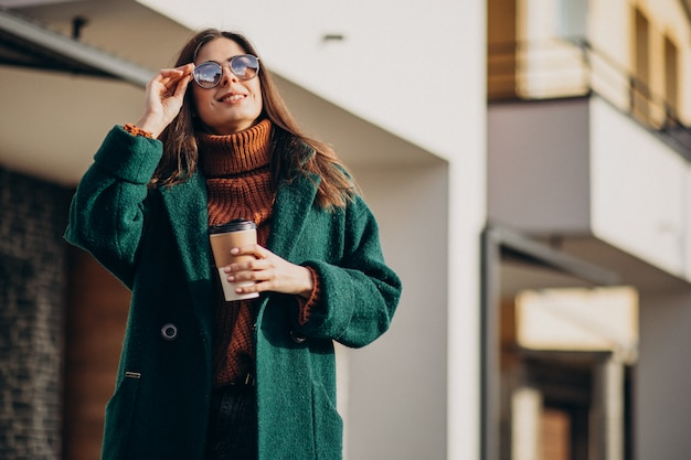 Trinkender kaffee der jungen frau durch das haus