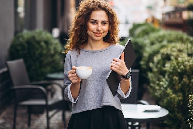 Trinkender kaffee der jungen geschäftsfrau außerhalb des cafés, das laptop hält