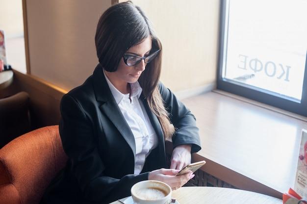 Trinkender kaffee der jungen geschäftsfrau im café und ablesen der telefonpost