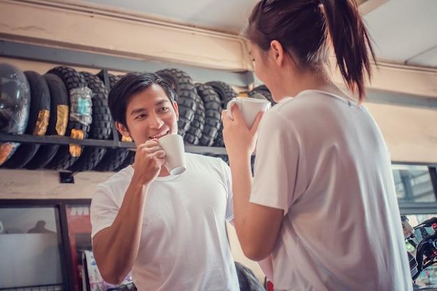 Trinkender kaffee der jungen paare und ein vertrauenswürdiges motorrad bevor dem reisen