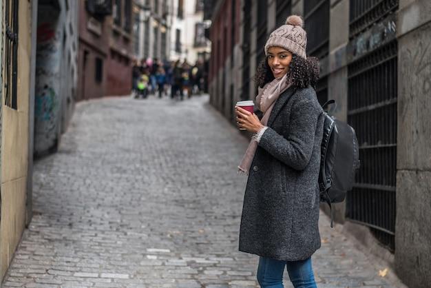 Trinkender kaffee der jungen schwarzen frau, der in die straßen von madrid auf winter wandert
