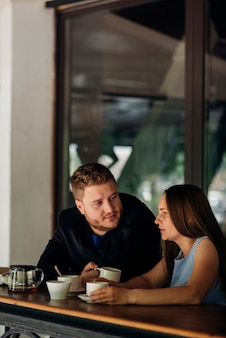 Trinkender kaffee der paare und unterhaltung in der kaffeestube