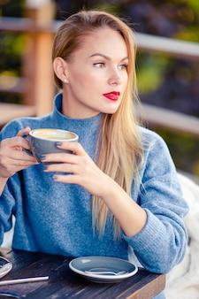 Trinkender kaffee der schönen frau im herbstpark unter herbstlaub