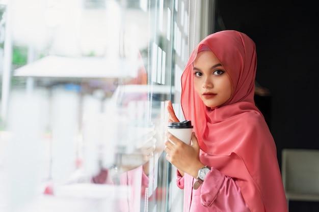 Trinkender kaffee der schönen jungen moslemischen geschäftsfrau am arbeitsplatz. porträt des jungen moslemischen rosa hijab am mitarbeiterraum.