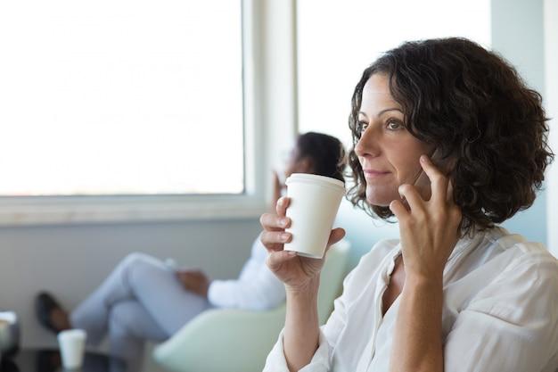 Trinkender kaffee der überzeugten geschäftsfrau bei der unterhaltung auf zelle