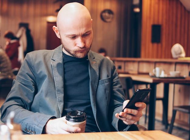 Trinkender kaffee des erwachsenen kahlen düsteren mannes von der papierschale und mit handy am café