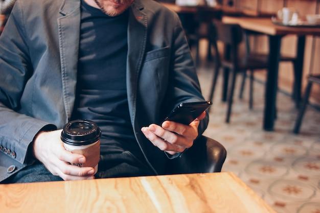 Trinkender kaffee des erwachsenen mannes von der papierschale und mit handy am café