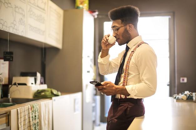 Trinkender kaffee des geschäftsmannes beim überprüfen seines telefons