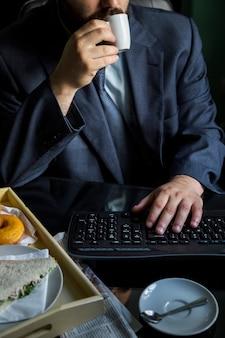 Trinkender kaffee des geschäftsmannes mit tastatur auf schreibtisch