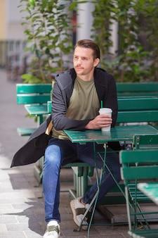 Trinkender kaffee des glücklichen jungen städtischen mannes in der europäischen stadt draußen