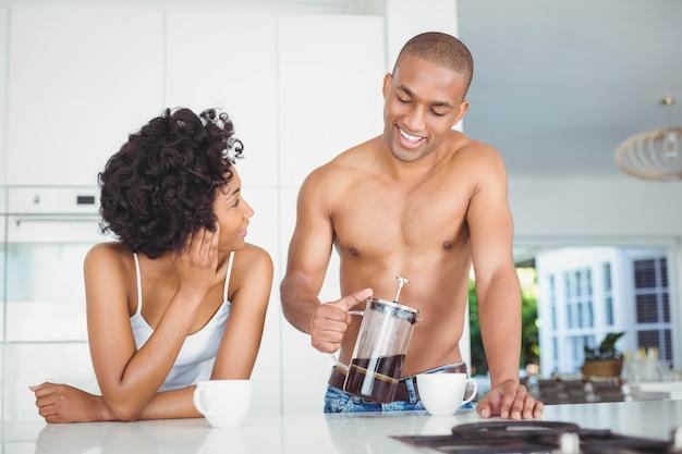 Trinkender kaffee des glücklichen paars in der küche zu hause