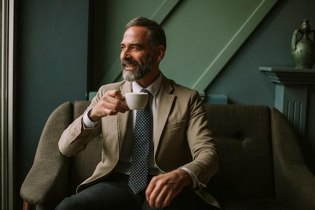 Trinkender kaffee des hübschen älteren geschäftsmannes in der lobby