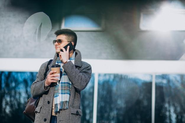 Trinkender kaffee des jungen gutaussehenden mannes draußen und mit telefon