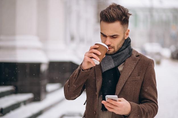 Trinkender kaffee des jungen gutaussehenden mannes und unterhaltung am telefon