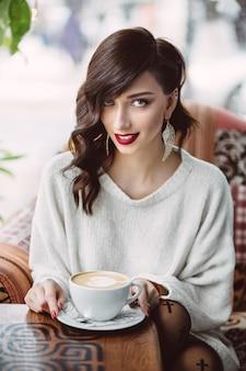 Trinkender kaffee des jungen mädchens in einem modischen café