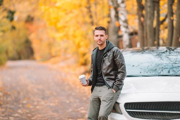Trinkender kaffee des jungen mannes mit telefon im herbstpark draußen