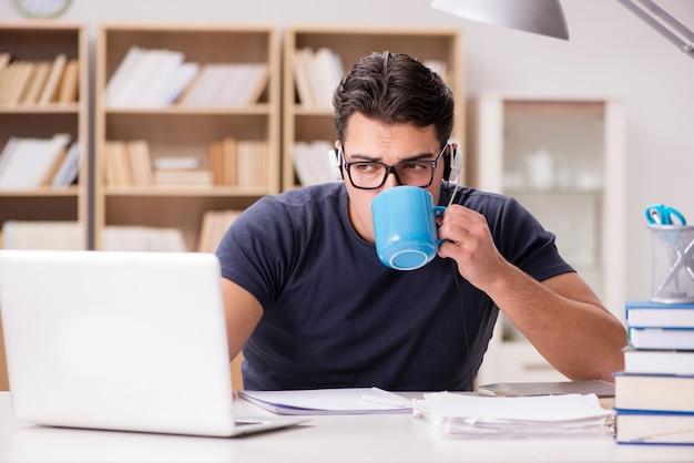 Trinkender kaffee des jungen studenten von der schale