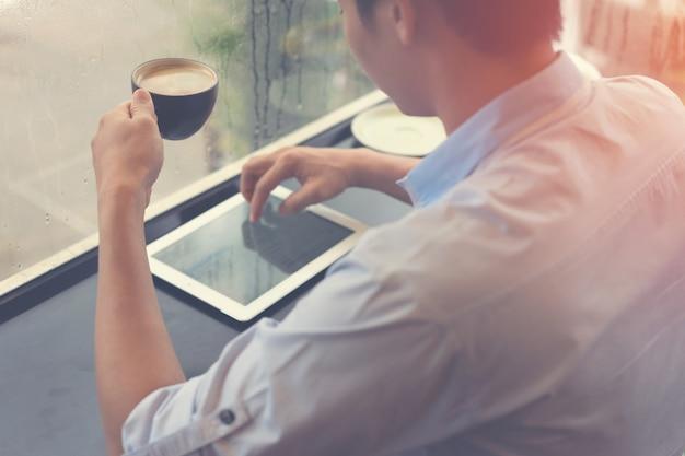 Trinkender kaffee des mannes und anwendung der tablette in der kaffeestube mit der entspannung