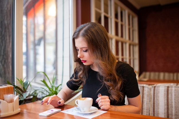 Trinkender kaffee des schönen mädchens und schauen im telefon