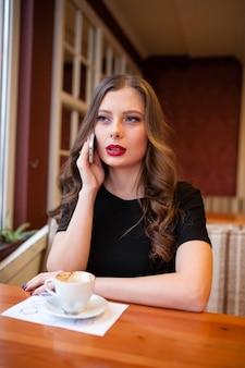 Trinkender kaffee des schönen mädchens und unterhaltung am telefon