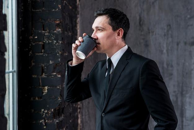 Trinkender kaffee des überzeugten geschäftsmannes von der papierschale
