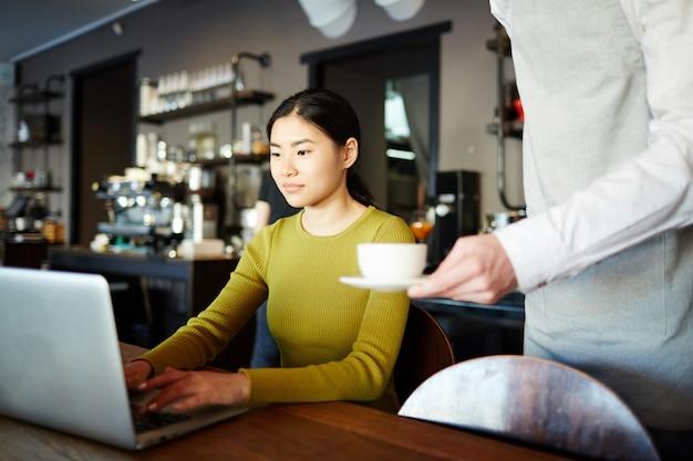 Trinkender kaffee oder tee der frau beim arbeiten an dem laptop