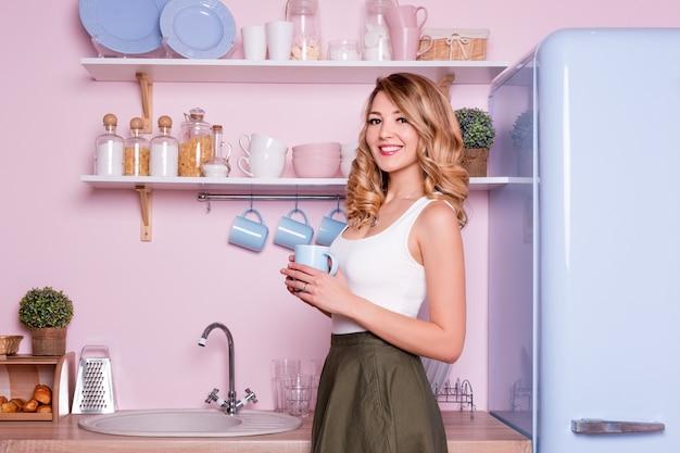 Trinkender kaffee oder tee der jungen glücklichen frau zu hause in der küche. blondes schönes mädchen, das ihr frühstückt, bevor es zum büro geht.