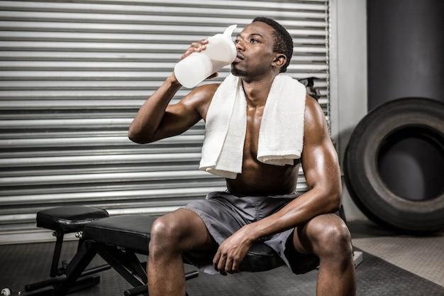 Trinkender proteindrink des hemdlosen mannes an der crossfit turnhalle