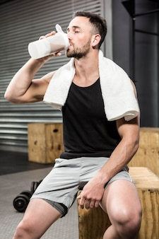 Trinkender proteindrink des muskulösen mannes an der crossfit turnhalle