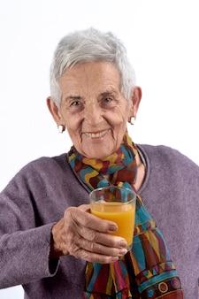 Trinkender saft der älteren frau auf weißem hintergrund