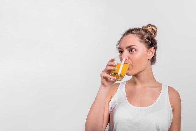 Trinkender saft der jungen frau vom glas