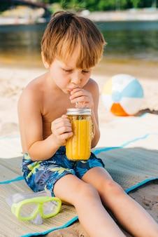 Trinkender saft des kleinen jungen auf strand