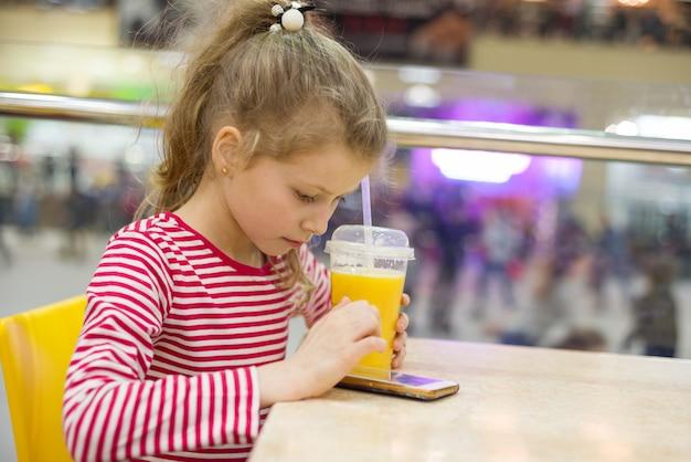 Trinkender saft des mädchenkindes im café unter verwendung eines smartphone