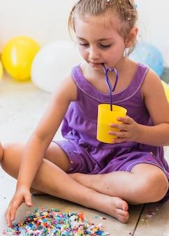 Trinkender saft des netten mädchens mit dem stroh, das konfetti auf fußboden erfasst