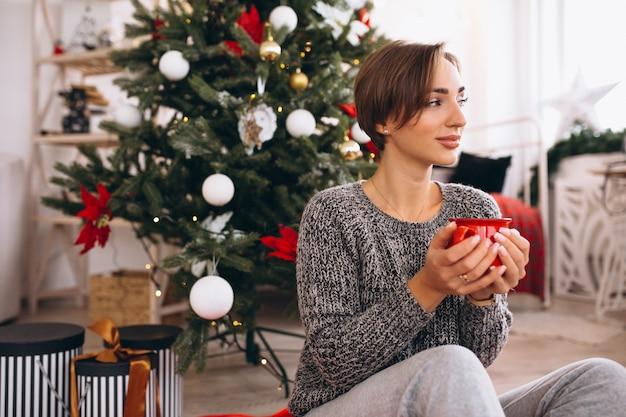 Trinkender tee der frau am weihnachtsabend