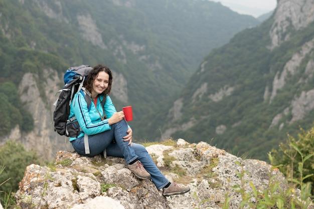 Trinkender tee der frau in den bergen.