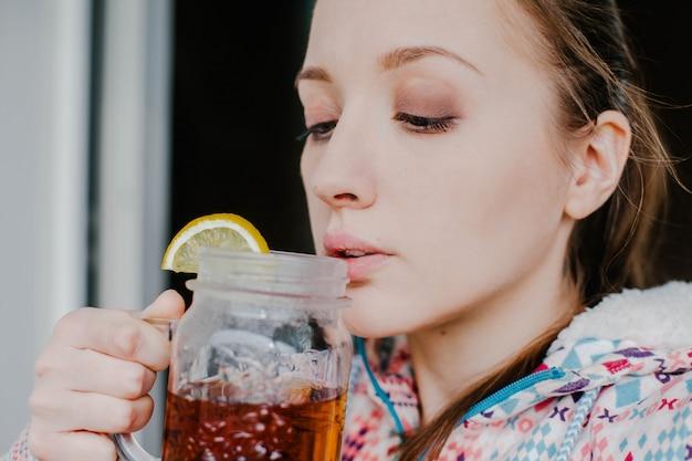 Trinkender tee der frau mit zitrone