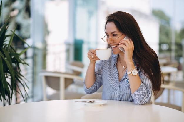 Trinkender tee der jungen dame in einem café