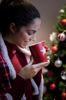 Trinkender tee der jungen frau der seitenansicht