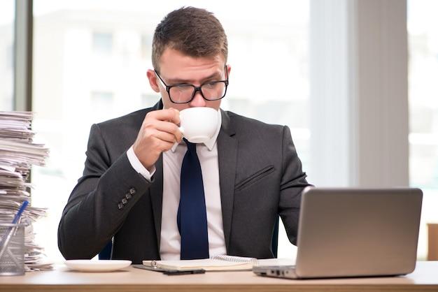 Trinkender tee des jungen geschäftsmannes im büro