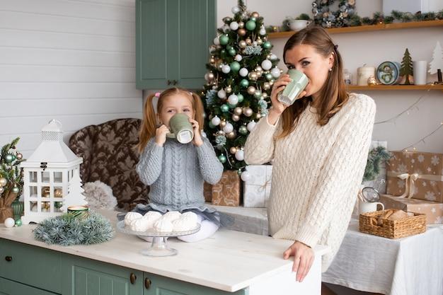 Trinkender tee des kleinen mädchens und der mutter in der weihnachtsküche zu hause.
