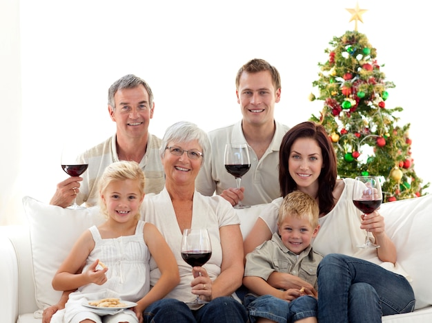 Trinkender wein der familie und bonbons im weihnachten essend