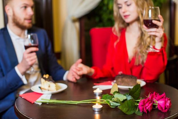 Trinkender wein der paare und händchenhalten bei tisch