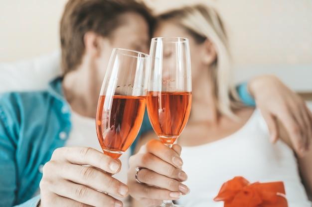 Trinkender wein des glücklichen paars im schlafzimmer