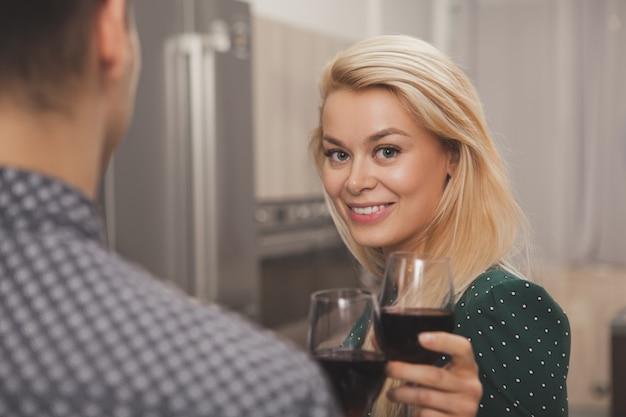Trinkender wein des glücklichen paars zusammen zu hause