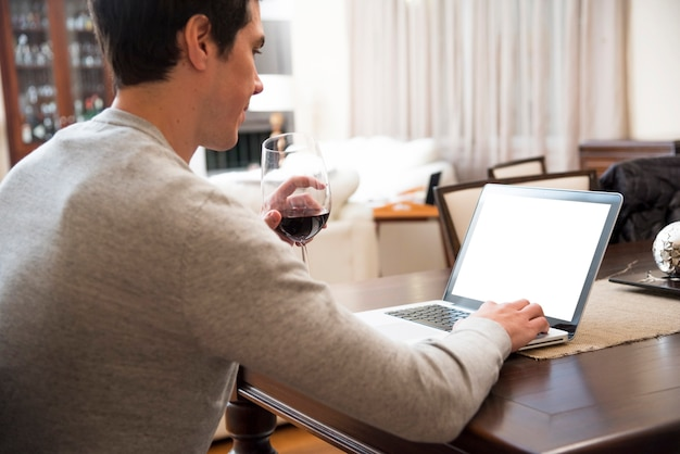 Trinkender wein des jungen mannes bei der digitalen tablette zu hause verwenden
