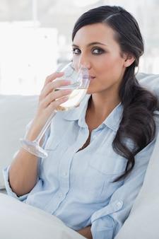 Trinkender weißwein des attraktiven brunette, der auf sofa sitzt
