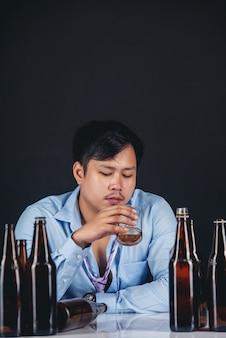 Trinkender whisky des alkoholischen asiatischen mannes mit vielen flaschen