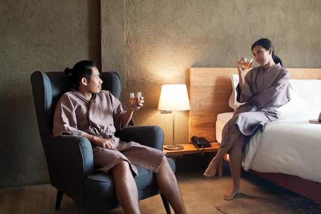 Trinkender whisky des asiatischen geliebten zusammen im schlafzimmer. lebensstil oder liebeskonzept